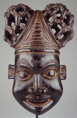 This Bamum mask symbolizes an ancestor and is worn at funerals and memorial celebrations. The masker places it on top of his head and wears a mesh veil to cover his face.